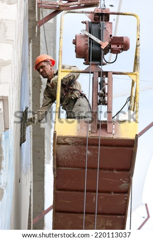 Plasterer builder man worker plastering house wall of bricks or concrete blocks during finishing construction works - stock photo