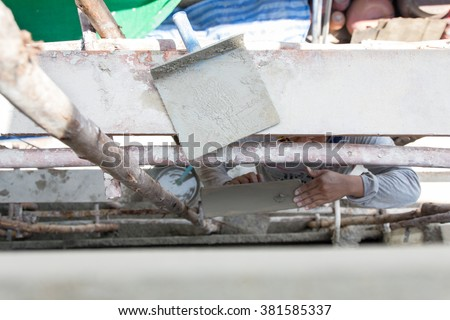 Plasterer cement concrete man worker stand on scaffold wood plastering wall of residential construction house - stock photo