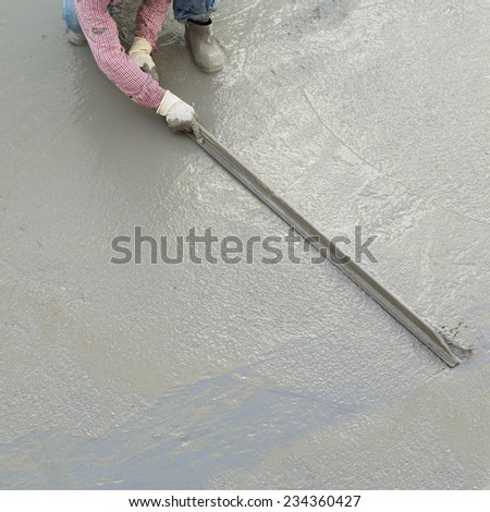 plasterer concrete cement worker plastering flooring of house construction - stock photo