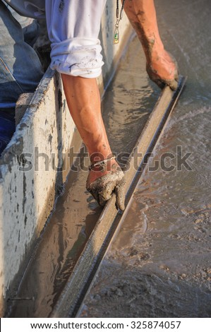 plasterer concrete cement worker plastering flooring of house construction evening of Thailand - stock photo