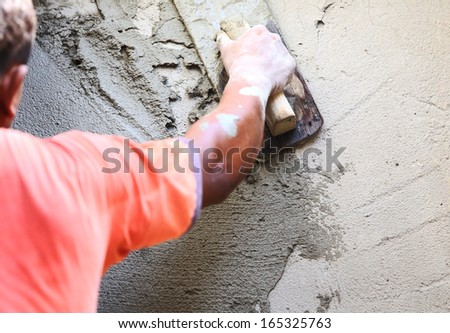 plasterer concrete worker at wall of house construction  - stock photo