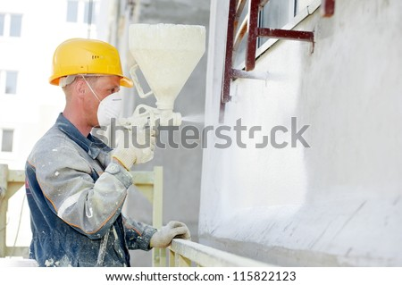 Plasterer facade builder worker with level at thermal insulation works - stock photo