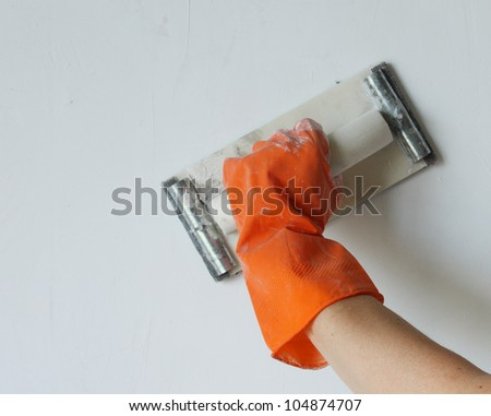Plasterer smoothing out wall with trowel - stock photo