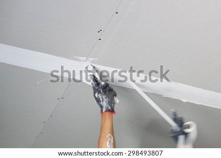 Plasterer spreading plaster to ceiling with trowel - stock photo