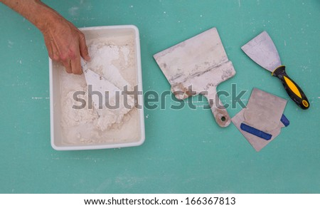 Plastering tools for plaster like plaste trowel spatula on green drywall plasterboard - stock photo