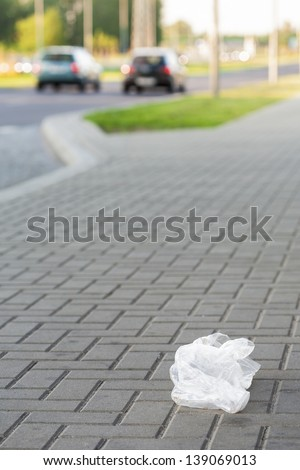 Plastic bag thrown on the street, littering the city.  - stock photo
