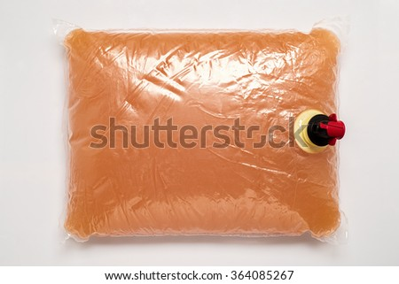Plastic bag with tap full of apple juice  - stock photo