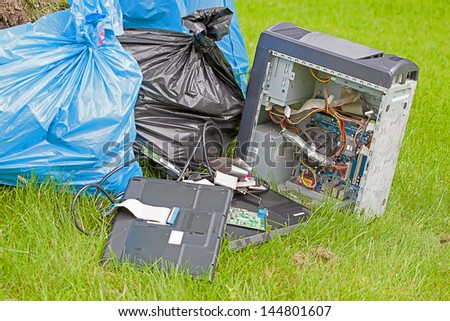 Plastic bags with garbage on the green grass - stock photo