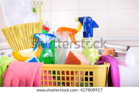 Plastic basket full of cleaning supplies and equipment in front of kitchen cabinets - stock photo