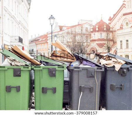 Plastic bins full of trash, old town background - stock photo