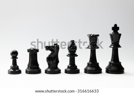 plastic black chess pieces in a row - pawn,rook,bishop,knight,queen,king - and white background - stock photo