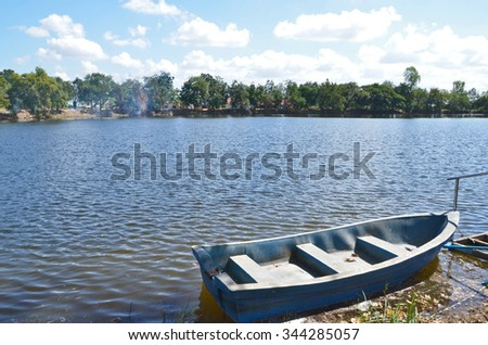 Plastic boat in the water beside the shore - stock photo