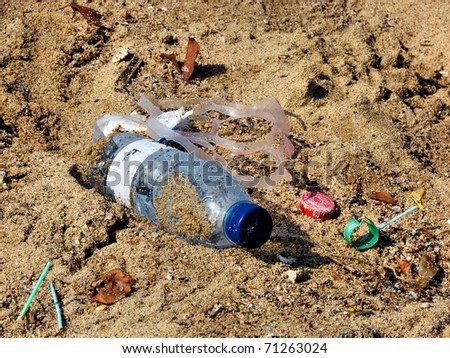plastic bottle and dust on beach sand - stock photo