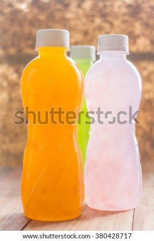 Plastic Bottle different of juice beverage on wooden table - stock photo