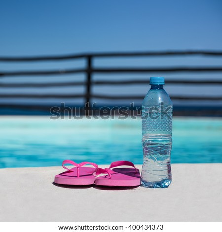 Plastic bottle with pure water and slippers near swimming pool at poolside - stock photo