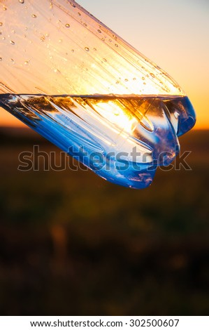Plastic bottle with water against the sunset sun. Beams of the sun make the way through water. - stock photo