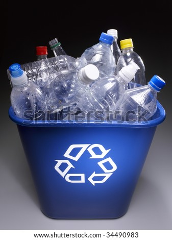 Plastic bottles in trash bin with recycle sign, elevated view - stock photo