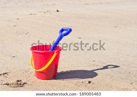 Plastic bucket and spade on a sandy beach - stock photo