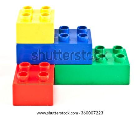 Plastic building blocks on white background. Bright colors. - stock photo