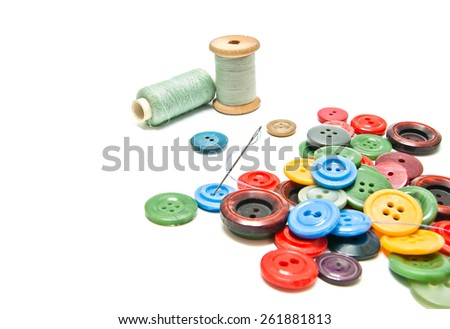 plastic buttons and spools of thread on white background - stock photo