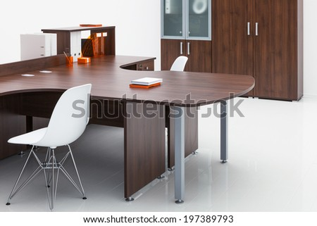 plastic chair, desk and bookcase on a white wall - stock photo