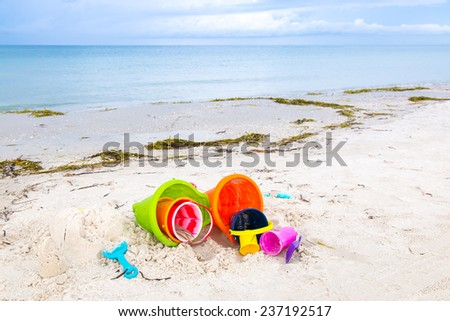 Plastic children toys on the sand beach, selective focus - stock photo