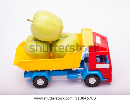 Plastic colorful toy truck yellow blue and red colors with three fresh green apple fruits in basket on white studio background closeup, horizontal picture - stock photo