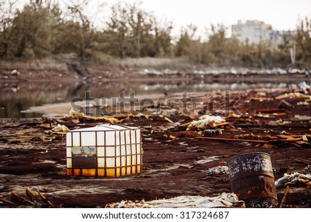Plastic containers and garbage lying on chemical contaminated waste - stock photo