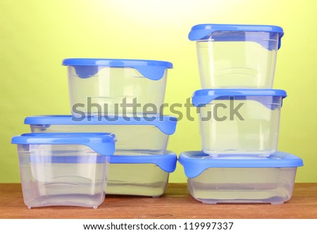 Plastic containers for food on wooden table on green background - stock photo