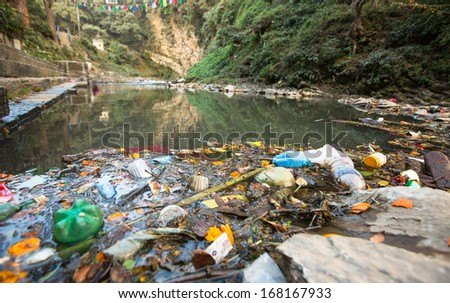 Plastic Contamination into Nature. Garbage and bottles floating on water. Environmental pollution in the Himalayas. Garbage in the water of river Bagmati. - stock photo
