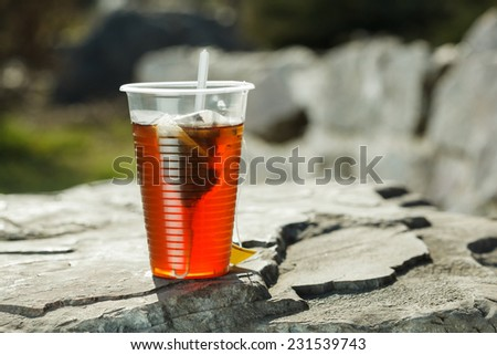 Plastic cup with black tea on big stone over nature background. - stock photo