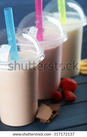 Plastic cups of milkshake on color wooden background - stock photo