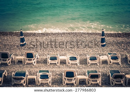 Plastic deckchairs and tables on a pebble beach with collapsed umbrellas - stock photo