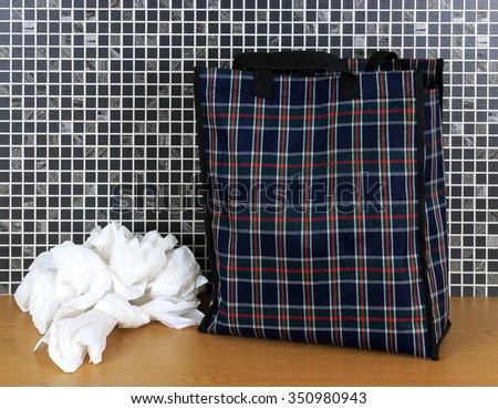 Plastic disposable bags and environmentally friendly re- usable tartan bag with dark mosaic tile background - stock photo