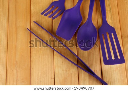 Plastic kitchen utensils on wooden background - stock photo