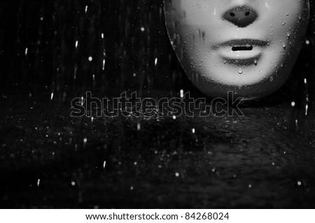 Plastic mask under the rain on a dark background - stock photo