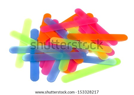 Plastic medical sticks (scapulas) of various colors for ENT doctor lying on white. Close-up. Isolated on white background. - stock photo