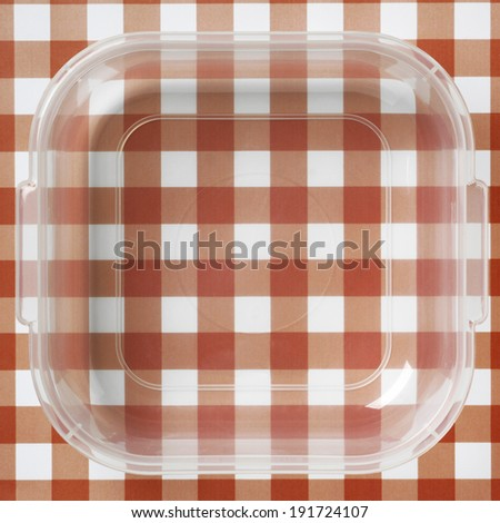Plastic packaging over a red and white tablecloths. Square format - stock photo