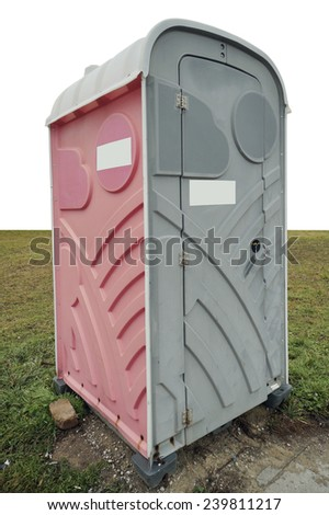 Plastic pink toilet cabin in a grass empty meadow isolated. Mass production - stock photo