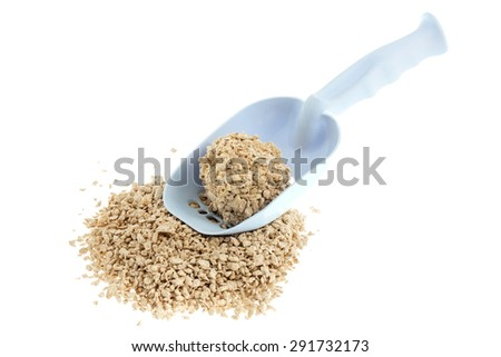 Plastic scoop for cleaning cat litter and a pile of filler on a  - stock photo