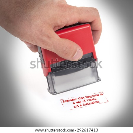 Plastic stamp in hand, isolated on white - Remember that happiness is a way of travel, not a destination - stock photo