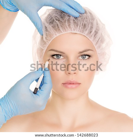 Plastic surgeon drawing lines over eyelid of a nice young female before cosmetic operation, isolated over white background. - stock photo