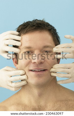 Plastic Surgeons Pulling Man's Skin back from Face - stock photo