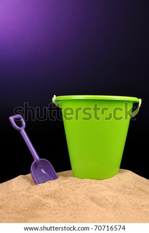 Plastic toy shovel and bucket in sand - stock photo