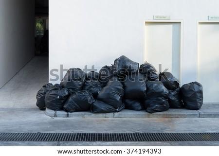 Plastic trash bags on outside street apartment - stock photo