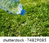 plastic water bottle on grass - stock photo
