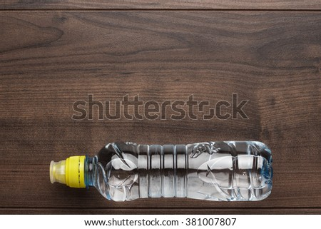 plastic water bottle with yellow cap on the wooden table - stock photo