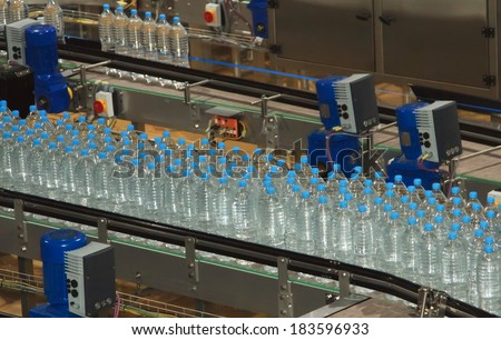 Plastic water bottles on conveyor and water bottling machine industry - stock photo