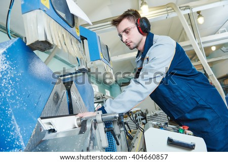 Plastic window and door manufacturing. Worker cutting PVC profile - stock photo