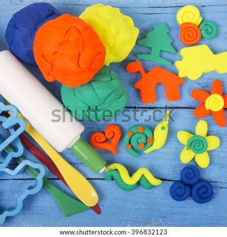 Plasticine and tools are on wooden background - stock photo